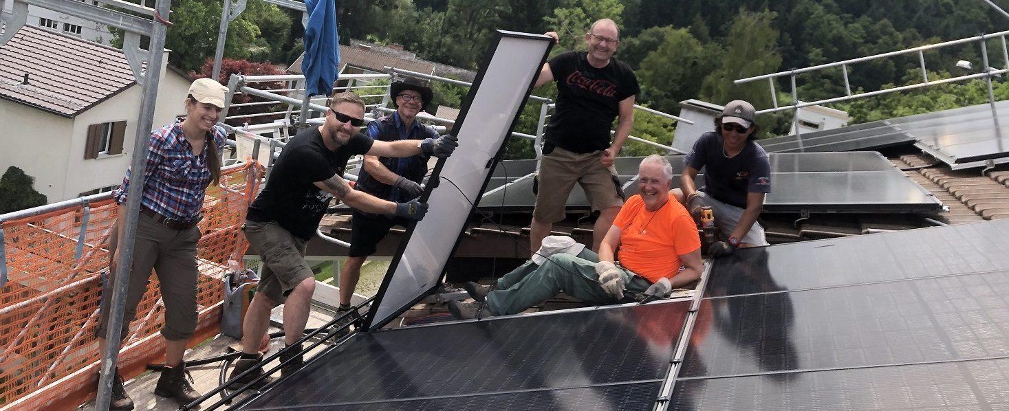 Vier Personen auf Dach mit Solarpanel